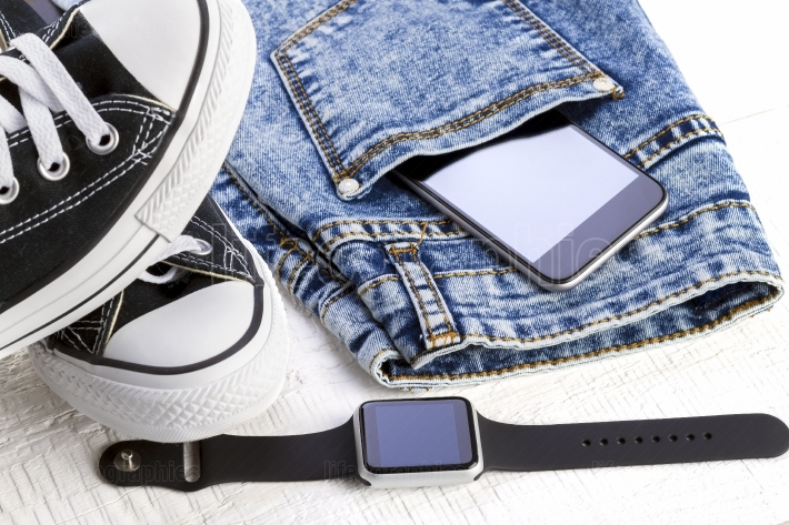 Smartphone in Jeans and fashion accessories on white wooden