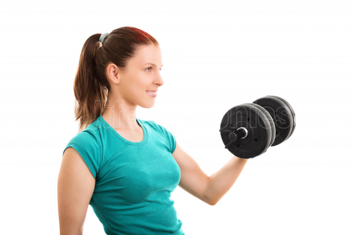 Smiling fit girl lifting a dumbbell