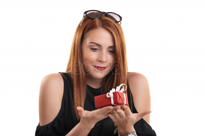 Smiling girl holding a small wrapped gift box
