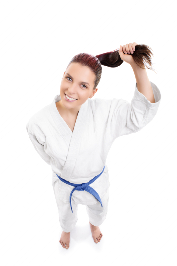 Smiling karate girl holding her ponytail