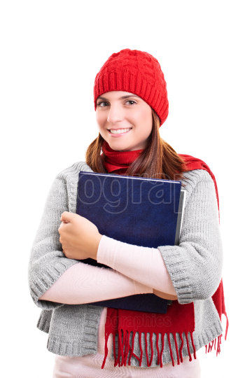 Smiling student in winter clothes holding a book