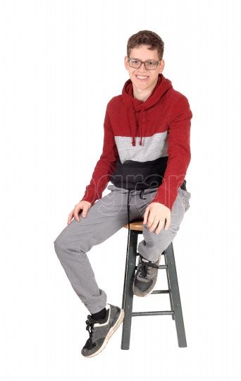 Smiling teen boy sitting on a chair