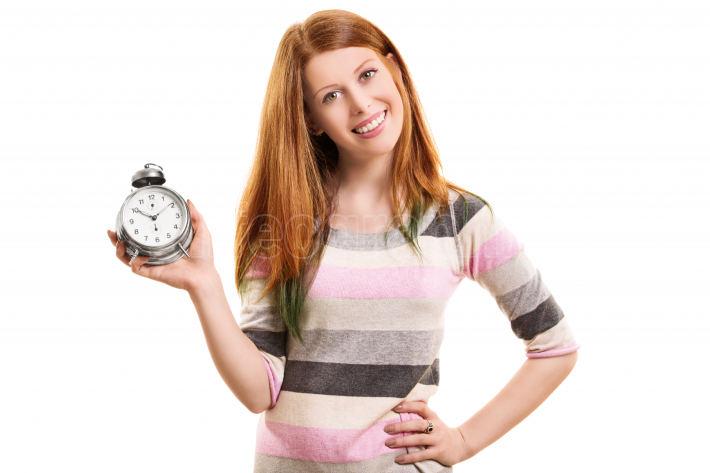 Smiling young girl holding an alarm clock