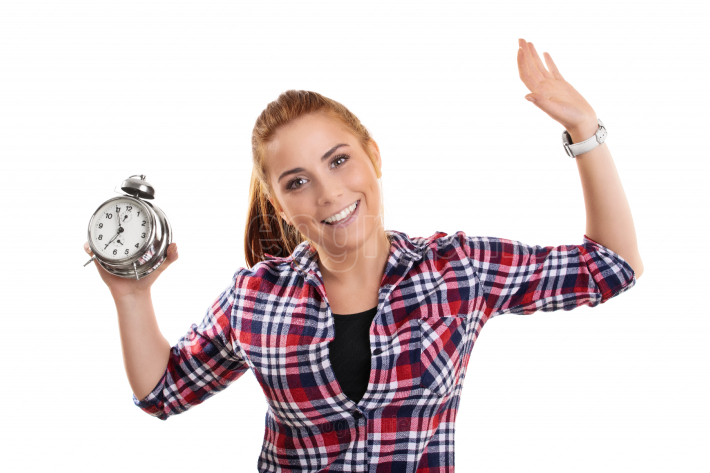 Smiling young girl holding an alarm clock with raised arms