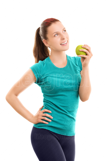 Smiling young girl in fitness clothes holding an apple