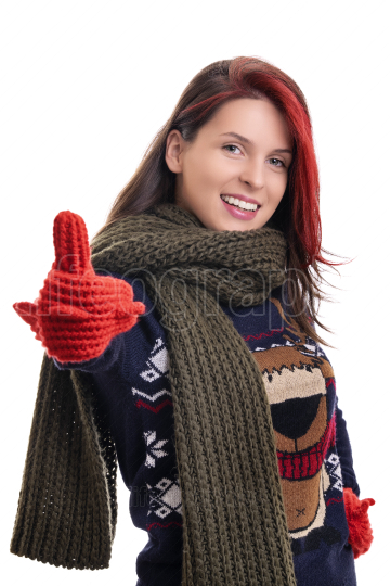 Smiling young girl in warm winter clothes giving thumbs up