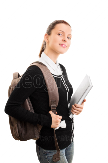 Smiling young girl wearing a backpack and some books