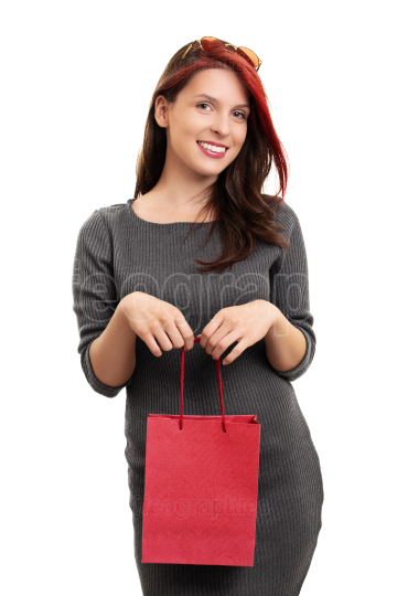 Smiling young girl with a shopping bag