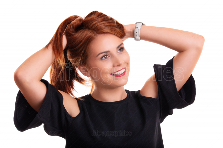 Smiling young redhead woman with hands in her hair