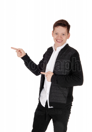 Smiling young teen boy standing, pointing with his fingers