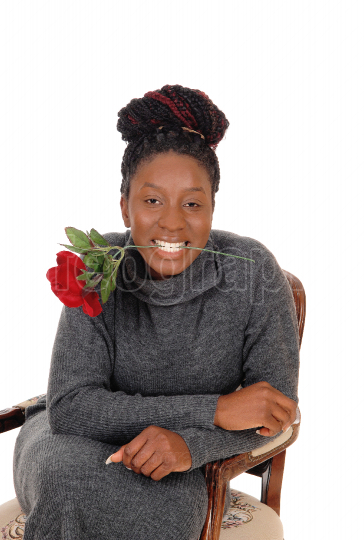 Smiling young woman sitting with a red rose
