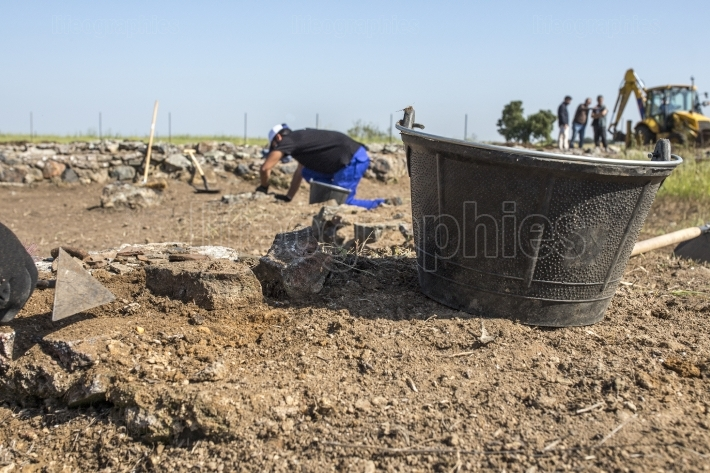 Specialized workers digging with trowel on archaeological excava