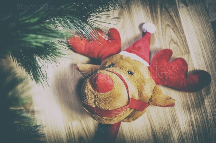 Stick plush reindeer toy close to Christmas Tree at home