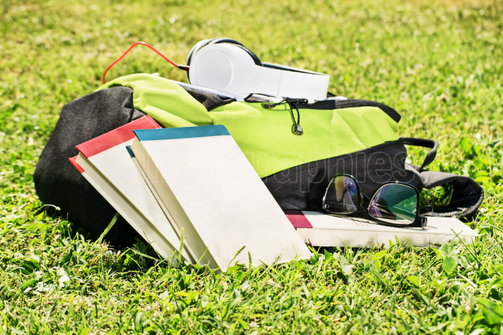 Student backpack with glasses, books and headphones