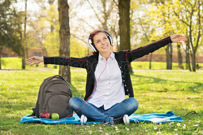 Student in a park with arms outstretched as if she s flying