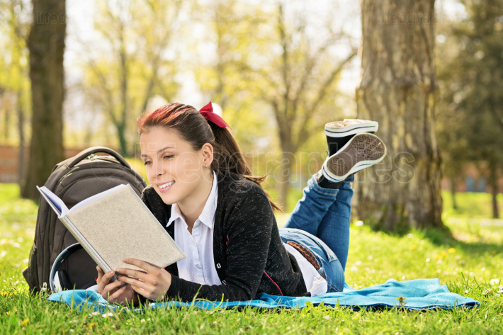 Student lying on a meadow reading a book