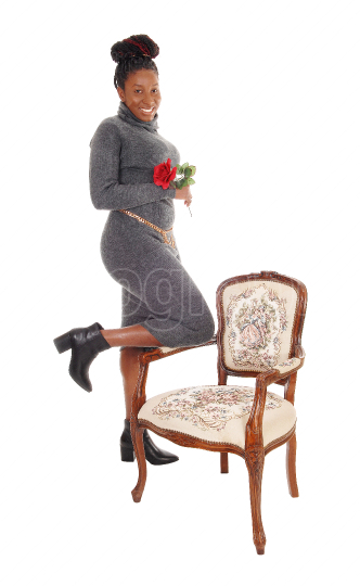 Tall gorgeous African woman standing on a chair