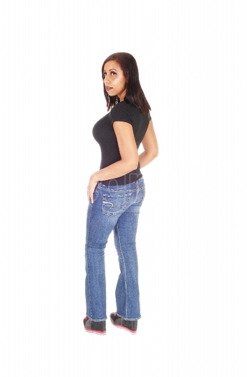 Tall woman standing in jeans from the back