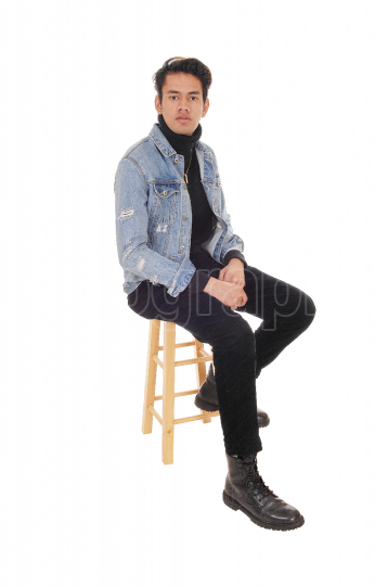 Tall young man sitting on a bar chair in a jacket