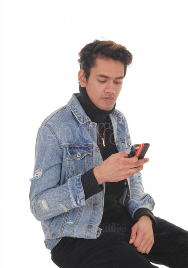 Tall young man sitting on a chair in a jeans jacket