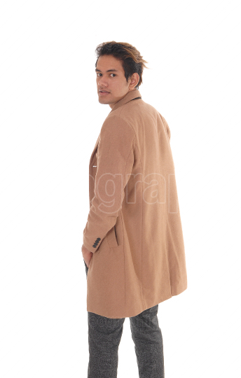 Tall young man standing in a beige coat from the back