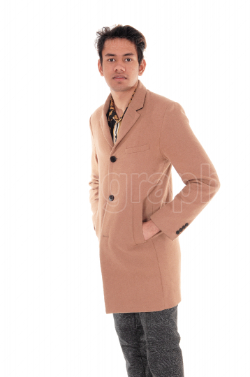 Tall young man standing in a beige coat in the studio