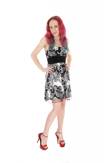 Tall young woman standing in short dress with red hair