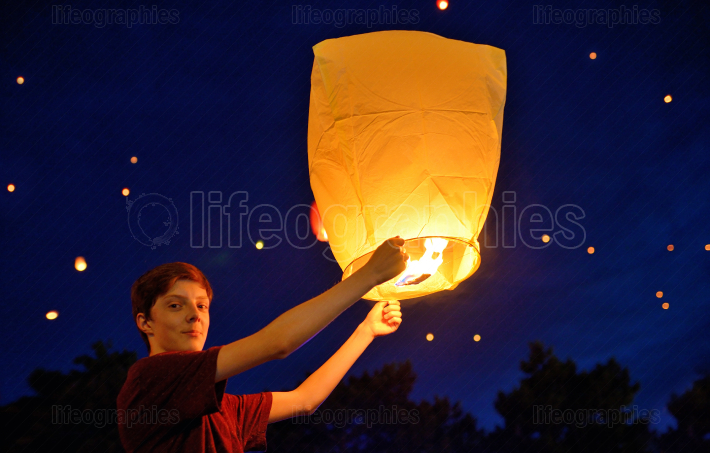 Teen boy in night with paper lantern