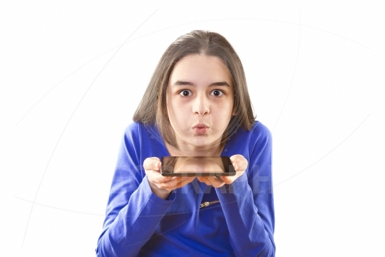Teenage girl blowing icons from digital tablet