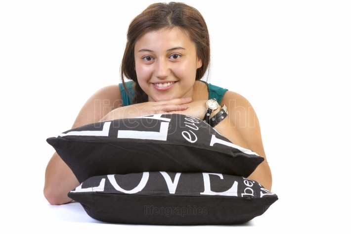 Teenage girl laying over pillow on white