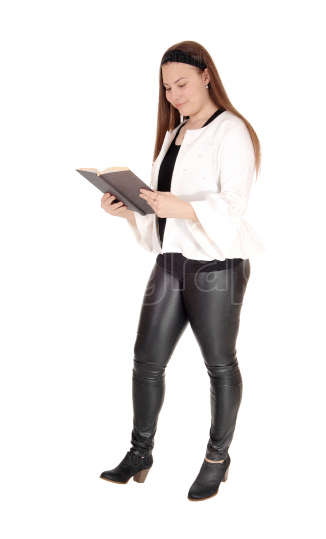 Teenage girl standing in pants holding a book in hands
