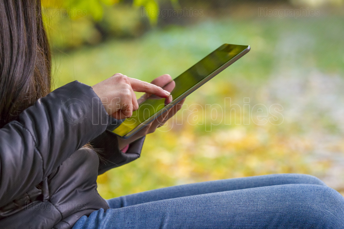 Teenage girl using digital tablet computer in autumn park