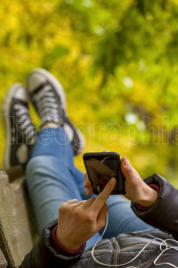 Teenage girl using smartphone in autumn park