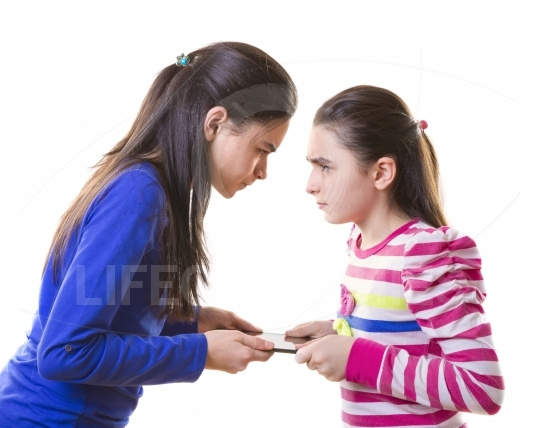 Teenage girls fighting for digital tablet