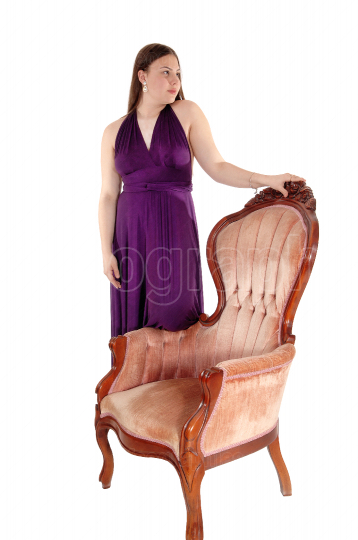 Teenager girl standing in her prom dress on armchair