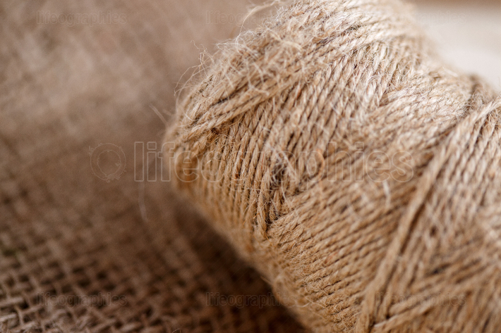 The canvas and the tangle of thread on a wooden background