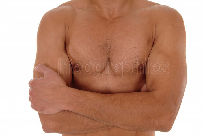 The chest of a young man with his arms crossed