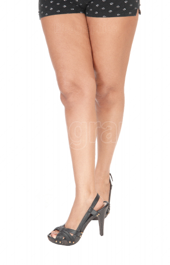 The long legs of a young woman in shorts