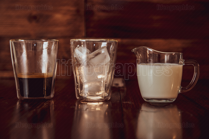 Three ingredients for coffee with ice are spread out over cups