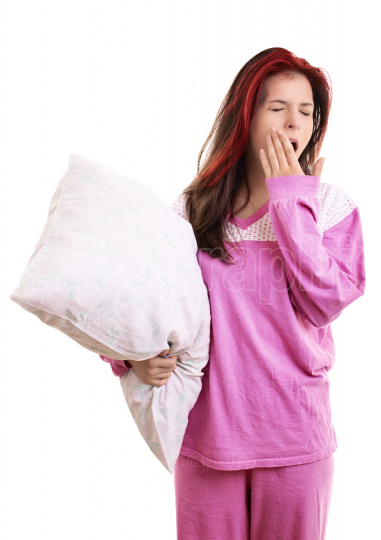 Tired young girl in pajamas holding a pillow and yawning