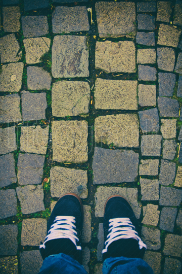 Top down view of feet in urban sneakers on cobblestones