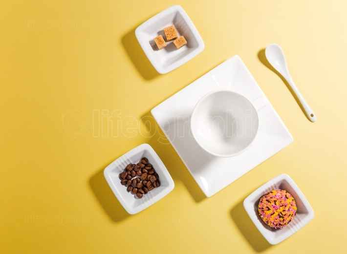 Top view of white porcelain with coffee beans, sugar and cake on