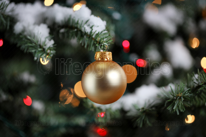 Traditional artificial Christmas tree with gold ball ornament wi