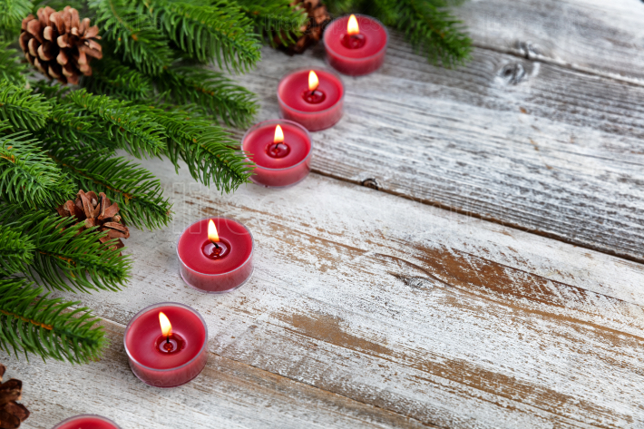Traditional Christmas holiday candles and evergreen branches on
