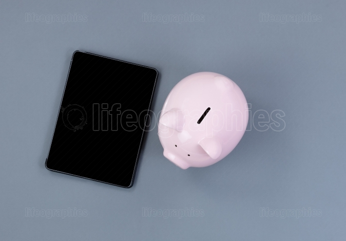 Traditional piggy bank and modern portable technology on gray de