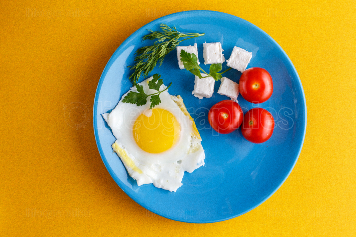 Turkish Breakfast on a blue plate on a bright yellow background