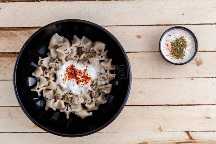 Turkish Manti manlama on plate with red pepper, tomatoes sauce,