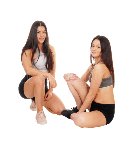 Two beautiful woman sitting on the floor in workout outfits