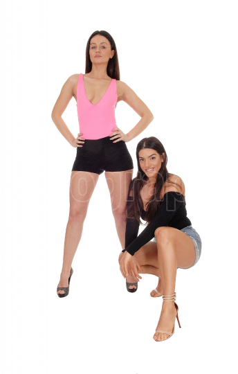 Two beautiful women standing and kneeling in shorts in the studi