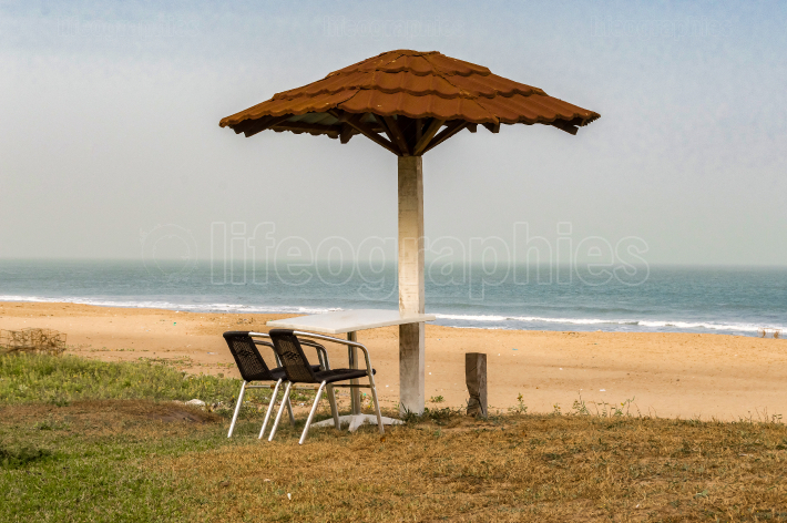 Two chairs and a table are placed facing the sea